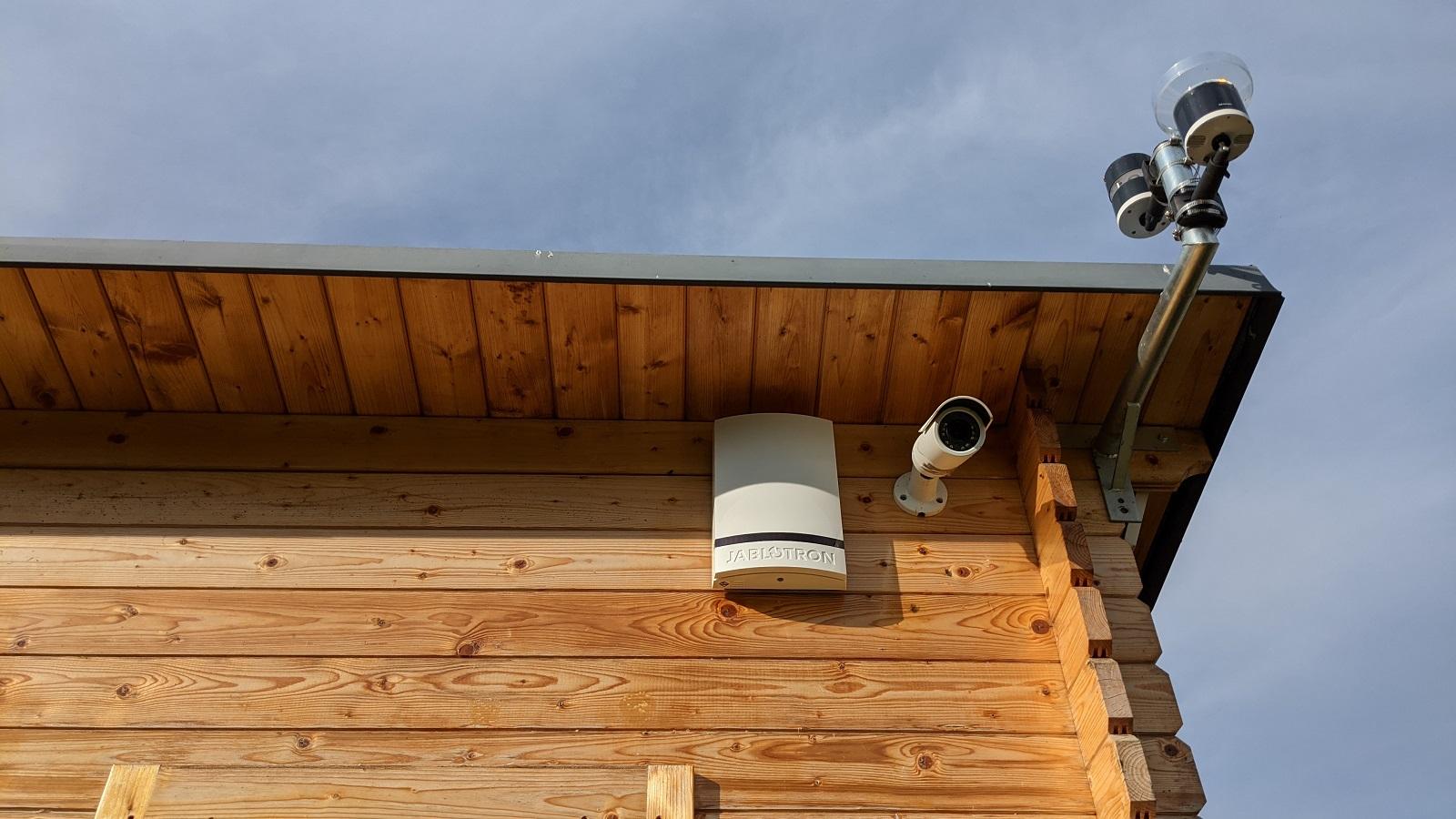 Venkovní siréna Jablotron vedle bezpečnostní kamery